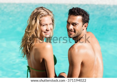 Rear view of couple sitting by the pool and looking back at the camera - stock photo