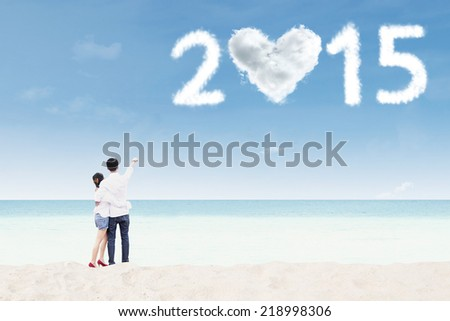 Rear view of couple standing on beach and pointing at cloud shaped heart and number 2015 - stock photo