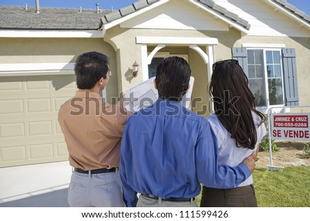 Rear view of couple with real estate agent explaining housing plan - stock photo
