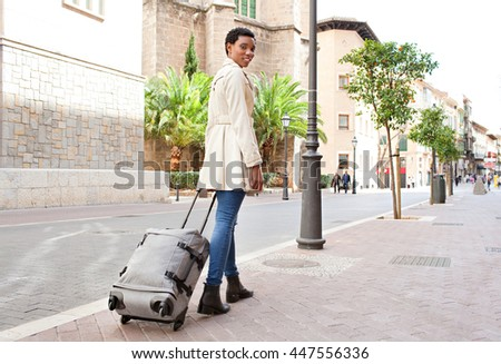 Rear view of elegant professional woman walking in a classic city street dragging a luggage suitcase, turning looking and smiling, outdoors. Tourist holiday in destination town exterior, lifestyle. - stock photo