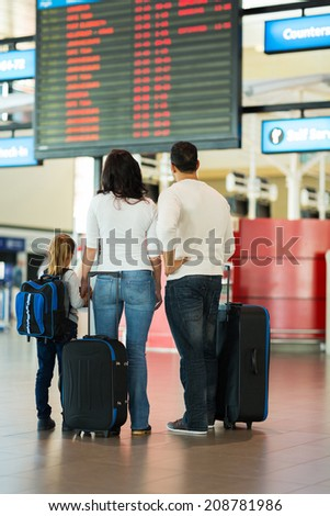 rear view of family checking flight information at airport - stock photo