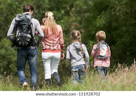 Rear View Of Family Hiking In Countryside - stock photo
