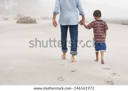 Rear view of father and son holding hands while walking on sand at beach - stock photo