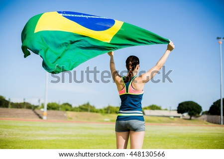 Rear view of female athlete holding an brazil flag in the air