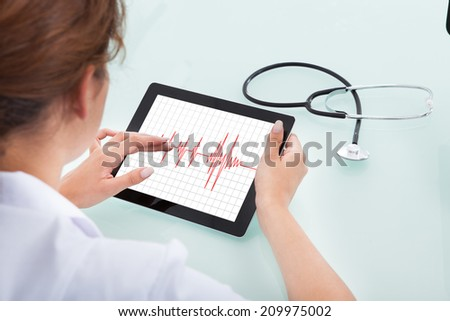 Rear view of female cardiologist analyzing heartbeat on digital tablet at desk - stock photo