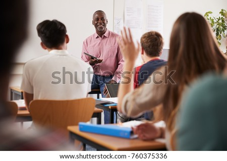 Rear View Of Female College Student Asking Question In Class