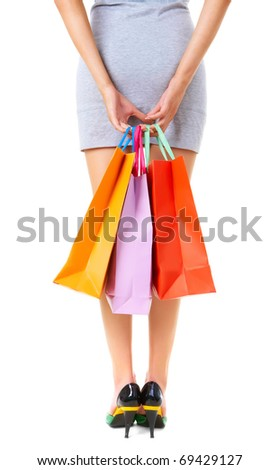 Rear view of female hands with colorful paperbags - stock photo