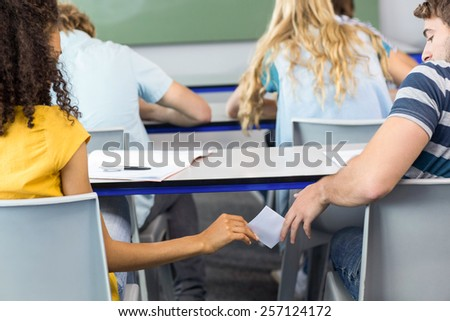 Rear view of female student passing note to friend in the classroom - stock photo
