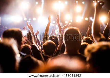 Rear view of festival crowd raising their hands. - stock photo