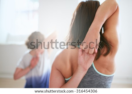 Rear view of fit woman doing gomukhasana in yoga class. Fitness female holding hands behind their back and stretching. Triceps and shoulders workout. - stock photo