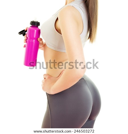 Rear view of fit young woman with water bottle. Closeup studio shot of fitness girl in gray sportswear holding pink bottle, unrecognizable, retouched, isolated on white, square format. - stock photo