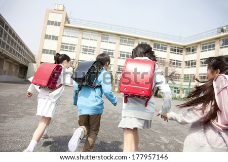 Rear View of four elementary leaving the - stock photo