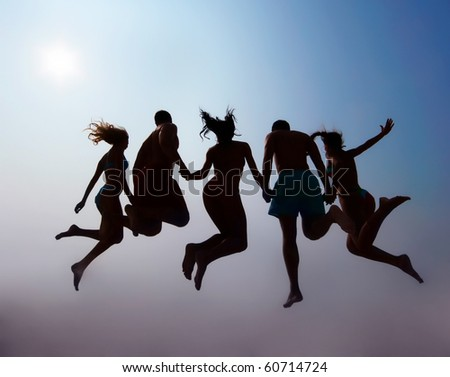Rear view of friends holding by hands and jumping on sandy beach against sky with sun on it - stock photo