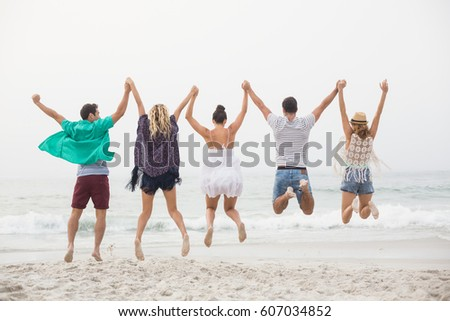 Rear view of friends holding hands and jumping in a row on the beach