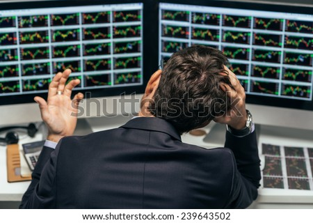 Rear view of frustrated stock trader looking at the financial graphs - stock photo