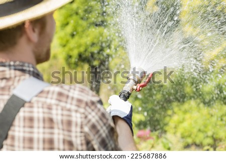 Rear view of gardener watering plants at garden - stock photo