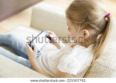Rear view of girl playing hand-held video game at home - stock photo
