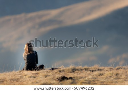 Rear view of girl sitting in a mountain meadow in fall season at sunset. Large copy-space at the top.