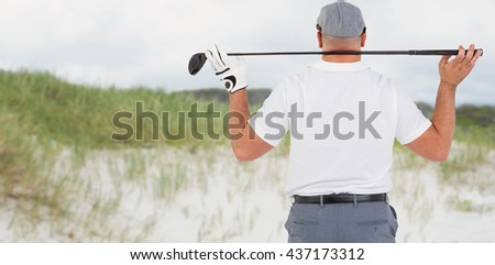 Rear view of golf player holding a golf club against view of sand - stock photo