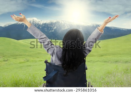 Rear view of handicapped woman enjoy freedom in the nature while sitting on wheelchair and raise hands - stock photo