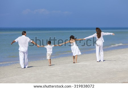 Rear view of happy family of mother, father and two children, son and daughter, walking holding hands and having fun in the sand on a sunny beach - stock photo