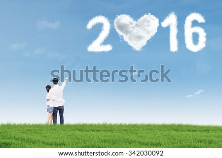 Rear view of happy young couple standing on the meadow while pointing at clouds shaped numbers 2016 - stock photo