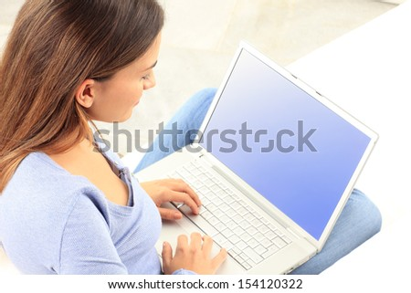 Rear view of happy young woman working on laptop at home - stock photo