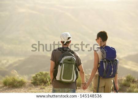 Rear view of hiking couple holding hands on top of mountain - stock photo