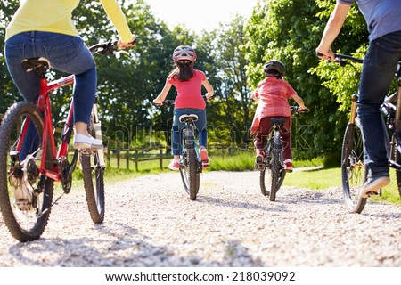 Rear View Of Hispanic Family On Cycle Ride In Countryside - stock photo