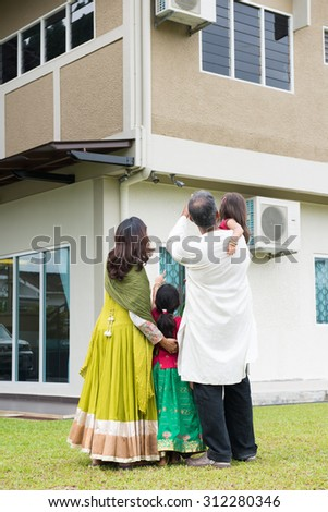 Rear view of Indian family in traditional dress saree standing outdoors and pointing to their new home.