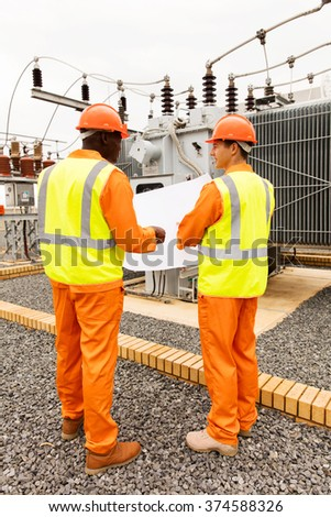 rear view of industrial engineers discussing blueprint at substation - stock photo