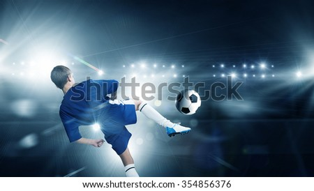 Rear view of kid boy in blue uniform on soccer stadium kicking ball - stock photo