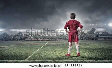 Rear view of kid boy in red uniform on soccer field - stock photo