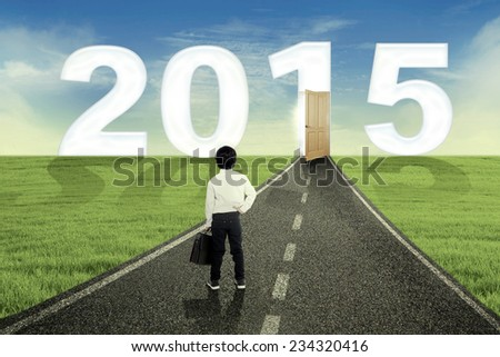Rear view of little businessman holding briefcase and standing on the road to his aim in the future 2015 - stock photo