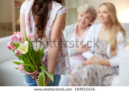Rear view of little girl holding bunch of flowers behind back with her mother and grandmother on background - stock photo