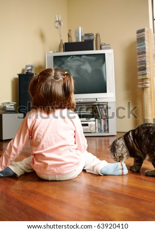Rear view of little girl sitting on the floor and watching TV with cat near by - stock photo