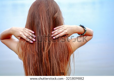 Rear view of long haired brunette posing against sea water on seaside - stock photo