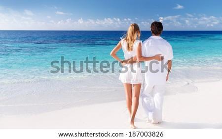 Rear view of loving couple enjoying seascape, active lifestyle, romantic feelings, honeymoon on luxury beach resort, summer vacation concept - stock photo