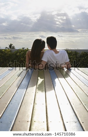 Rear view of loving teenage couple sitting on deck looking at view - stock photo