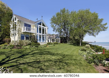 Rear view of luxury home along lake shore - stock photo