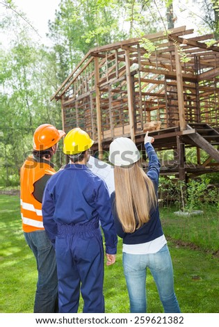Rear view of male and female architects discussing over incomplete wooden cabin at construction site - stock photo