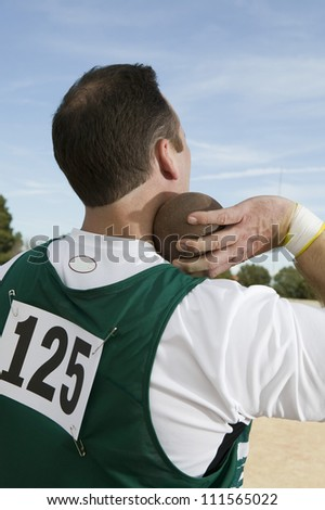 Rear view of male athlete ready to throw shot put - stock photo