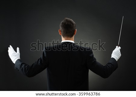 Rear view of male music conductor holding baton against gray background - stock photo