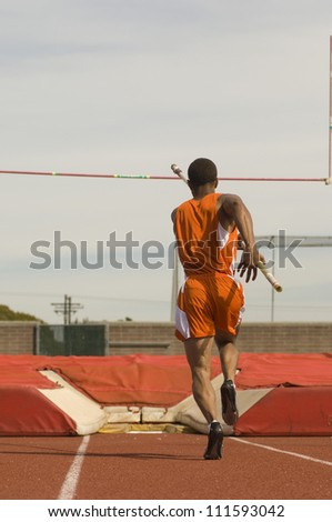 Rear view of male pole vaulter running with pole - stock photo