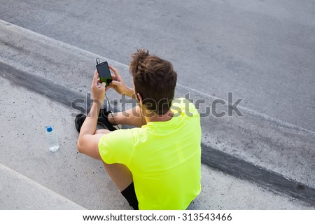 Rear view of male runner in bright t-shirt using mobile phone while taking break after active intense training outdoors, young sports man use smart phone with blank copy pace screen for text message - stock photo