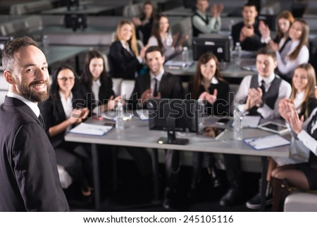 Rear view of male speaker on the podium. He is looking at the camera. People at the modern conference hall. - stock photo