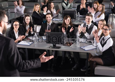 Rear view of male speaker on the podium. People at the modern conference hall. - stock photo