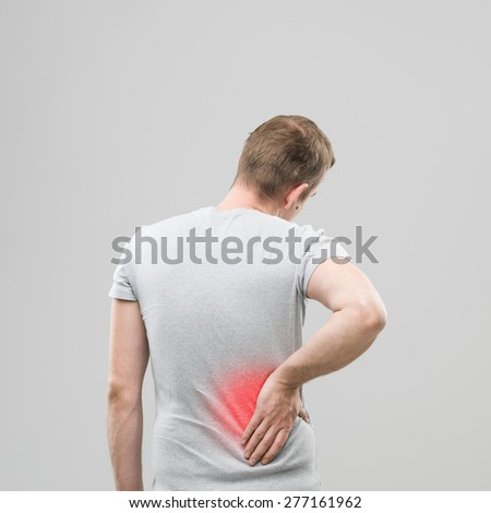 rear view of man experiencing back pain, with red spot marking the injured area - stock photo