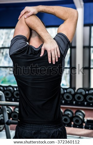 Rear view of man stretching arms at gym - stock photo