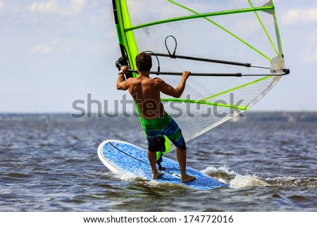 Rear view of man windsurfing in splashes of water - stock photo